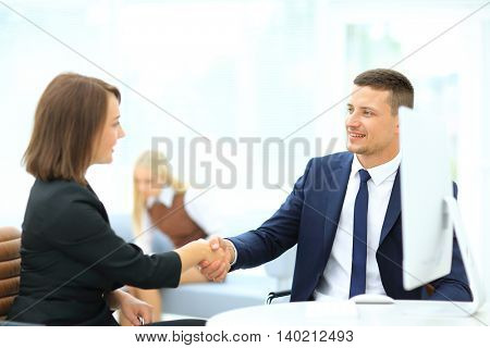 Business partners shaking hands in meeting hall