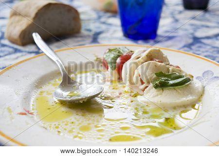 Caprese salad made of sliced fresh mozzarella tomatoes and green basil seasoned with salt olive oil