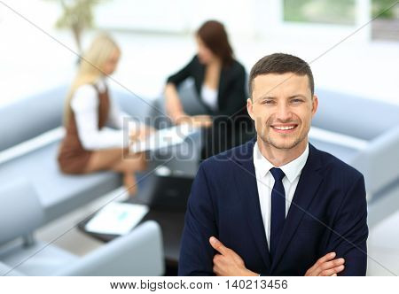 Smiling business man standing with his collegues in background a