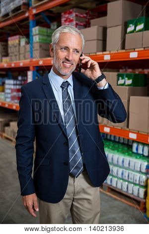 Business man calling on the phone in a warehouse
