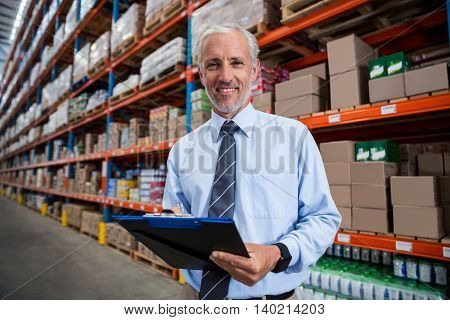 Worker holding clibpoard in a warehouse