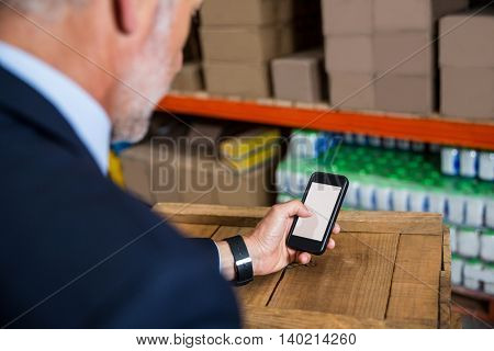 Business man using his smartphone in a warehouse