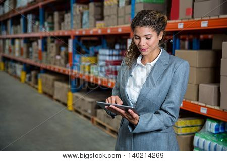 Business woman using tablet in a warehouse