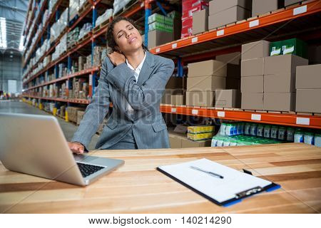 Business woman has a back pain in a warehouse