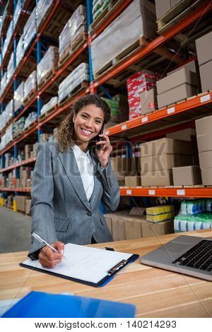 Business woman calling on her desk in a warehouse