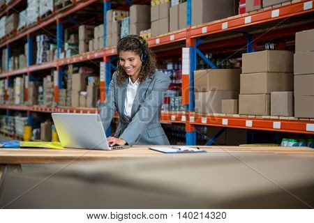 Business woman is talking with a headset in a warehouse
