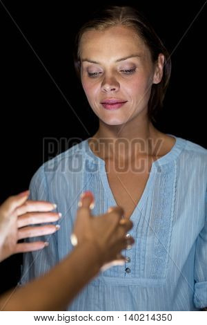 Cropped image of hypnotist hypnotizing woman against black background