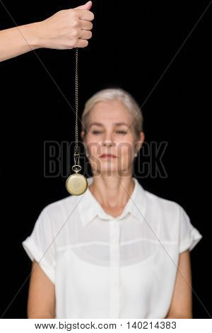 Cropped image of hypnotherapist holding pendulum before woman against black background