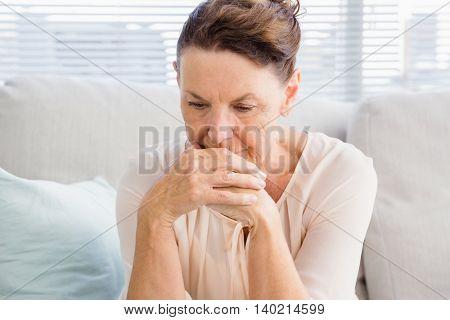 Sad mature woman sitting on sofa at home