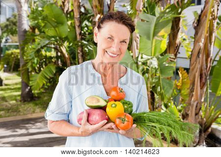 Portrait of cheerful woman holding fruits and vegetables