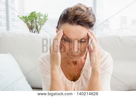 Close-up of irritated woman suffering from headache while sitting at home