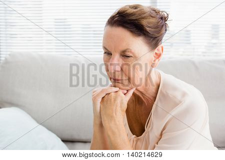 Close-up of thoughtful woman with hands on chin while sitting on sofa