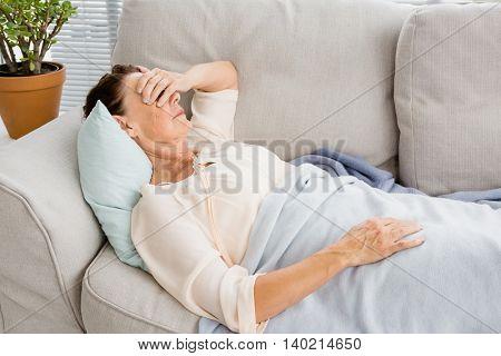 Mature woman having headache while lying on sofa at home