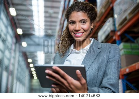 Business woman using her tablet in a warehouse
