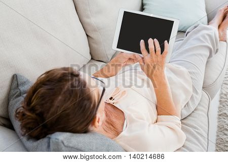 Woman using digital tablet while resting on sofa at home