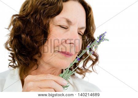 Close-up of mature woman smelling flowers against white background