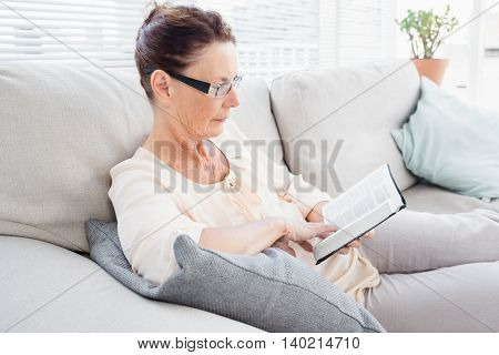 Concentrated mature woman reading book while resting on sofa at home