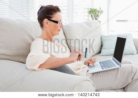 Woman carrying laptop while resting on sofa at home