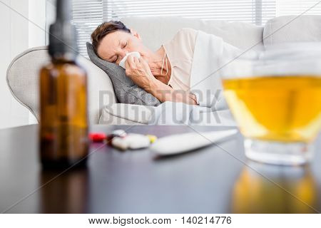 Woman sneezing while lying on sofa with herbal tea and medicine on foreground