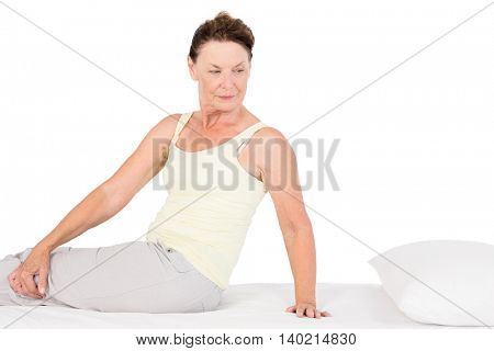 Confident mature woman exercising on bed against white background