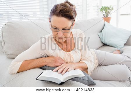 Mature woman reading book while resting on sofa at home