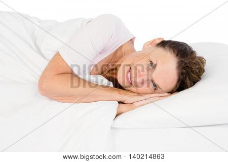 Portrait of smiling mature woman lying on bed against white background
