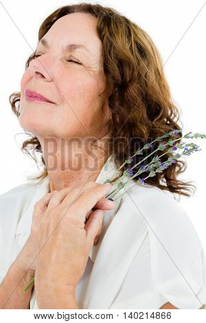 Mature woman holding flowers against white background