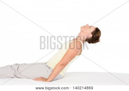 Calm woman exercising on bed against white background