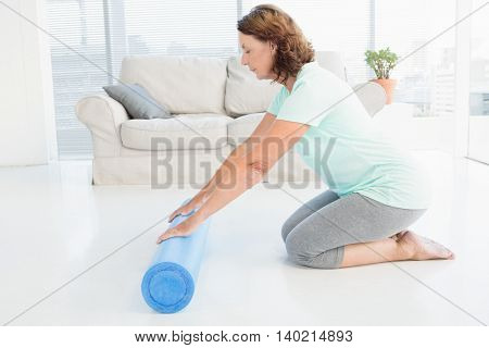 Mature woman rolling exercise mat at home