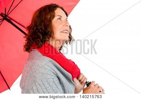 Thoughtful mature woman holding umbrella while standing against white background