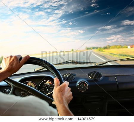 Driver's hands on a steering wheel of a car and blue sky with clouds