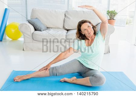 Mature woman stretching on exercise mat at home