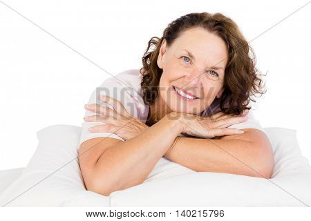 Portrait of confident woman lying on bed against white background