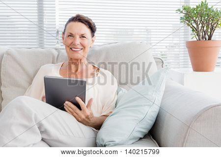 Portrait of happy mature woman holding digital tablet while sitting on sofa at home