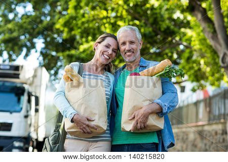 Portrait of mature couple holding shopping bags while standing by tree