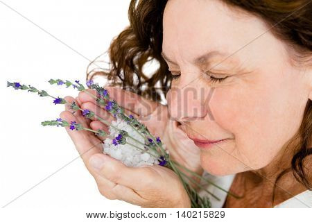 Close-up of smiling mature woman smelling flowers while standing at spa