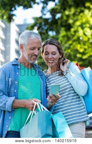 Smiling mature couple using mobile phone while holding shopping bags in city