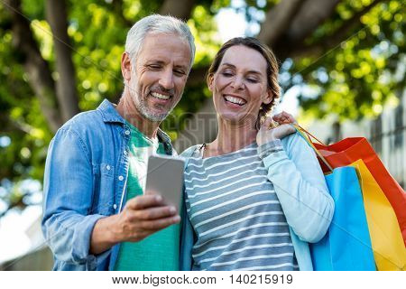 Happy mature couple using mobile phone while holding shopping bags by tree