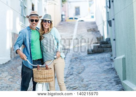Portrait of mature couple with bicycle walking on street amidst buildings