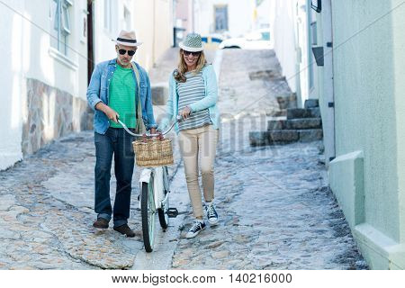 Mature couple with bicycle walking on street amidst buildings