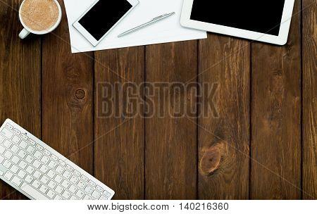Smartphone, tablet, coffee and paper on wooden table