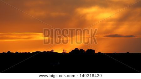 Sun set on the Pennines, taken on a July evening in West Yorkshire, UK, showing the silhouetted horizon, trees, and landscape. The sun having set beyond an electricity pylon, the sky a variety of colours - initially grey clouds and yellow and orange burst