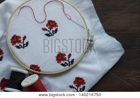 White cloth with hand-embroidered with a cross in the hoop on a wooden table top view