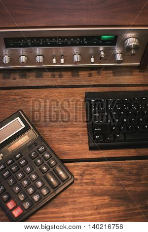 vintage receiver and a calculator on a wooden background.