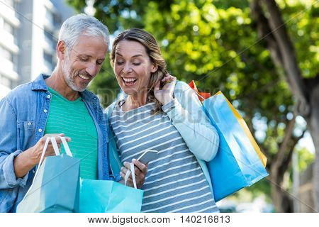 Happy mature couple using mobile phone while holding shopping bags in city