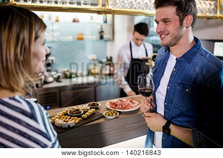 Happy couple talking while having wine by bar counter at restaurant