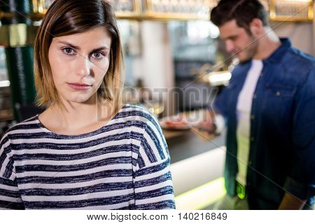 Portrait of upset woman with boyfriend in background at bar