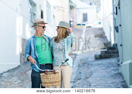 Happy mature couple with bicycle standing on street amidst buildings