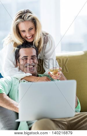 Romantic Mid adult couple using laptop at home
