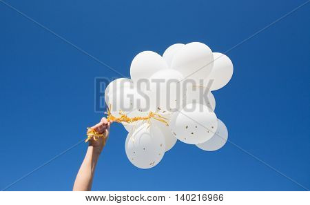 holidays, birthday, party and people concept - close up of hand holding bunch of inflated white helium balloons over blue sky